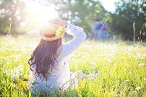 草原に帽子かぶった女性